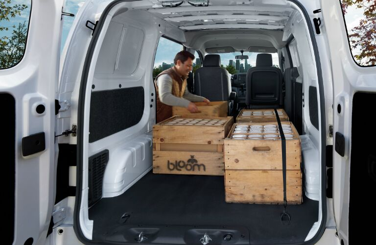 A man loading crates in a 2019 Nissan NV200 Compact Cargo Van