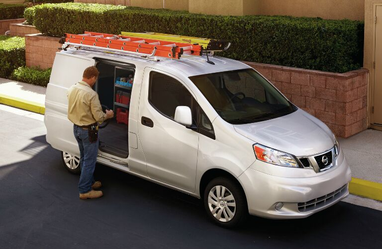A man standing next to the sliding door of a white 2019 Nissan NV200 Compact Cargo Van