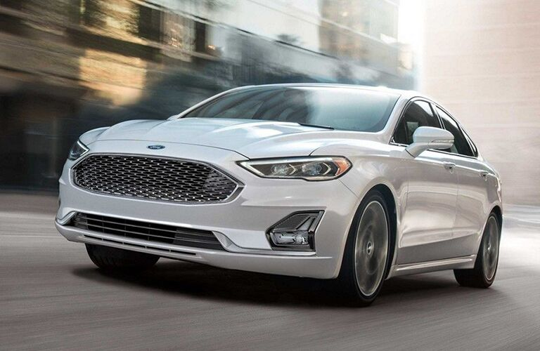 Front driver angle of a white 2019 Ford Fusion driving down a road