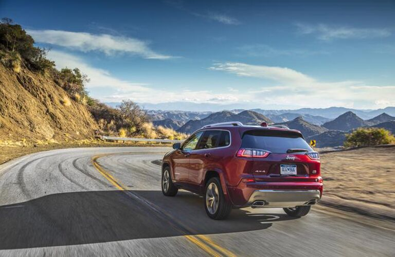 A rear image of a red 2020 Jeep Cherokee driving down a rural road.
