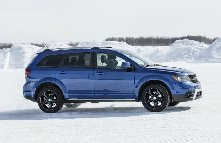 Blue 2020 Dodge Journey driving on a snowy surface