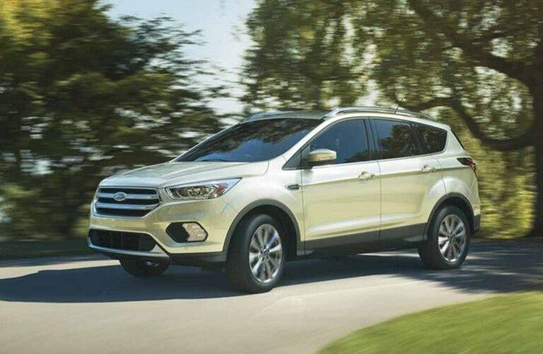 Profile view of white 2019 Ford Escape driving through parkway
