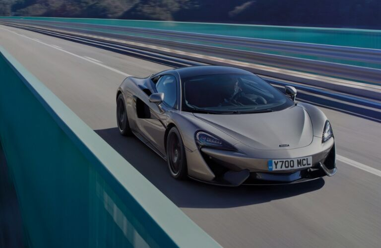 Front view of silver 2019 McLaren 570S driving across a bridge