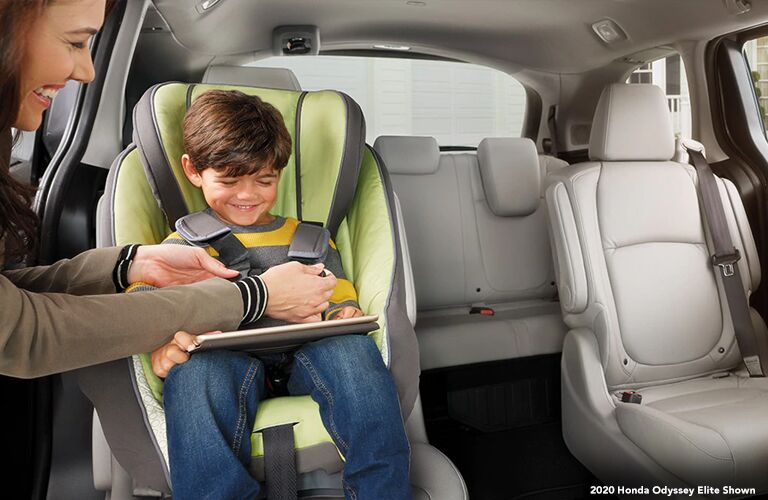Mother buckling her kid into a booster seat in the 2020 Honda Odyssey Elite
