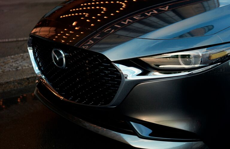 The front grille and headlights on a gray 2021 Mazda3 Sedan.