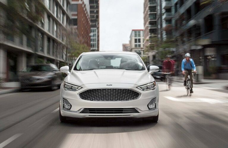 Front angle of a white 2019 Ford Fusion Hybrid driving down a city street