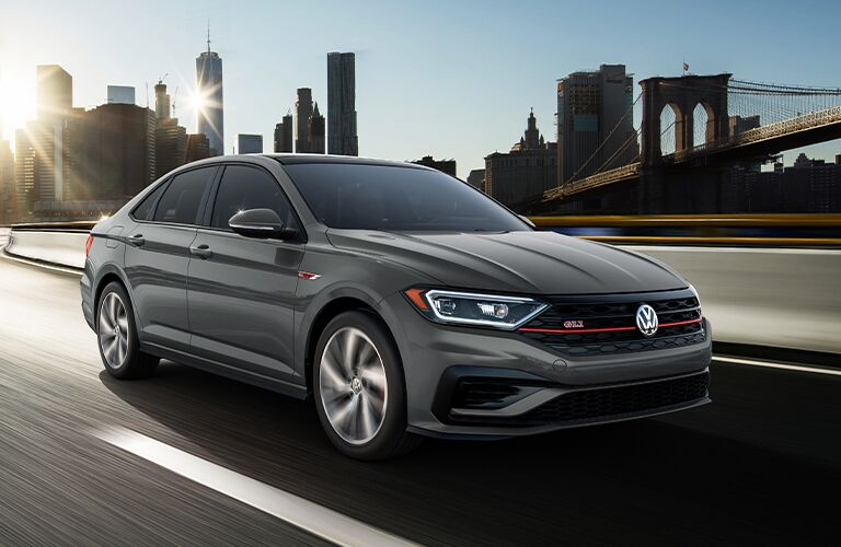 A 2021 Volkswagen Jetta GLI driving down a road with a city landscape in the background