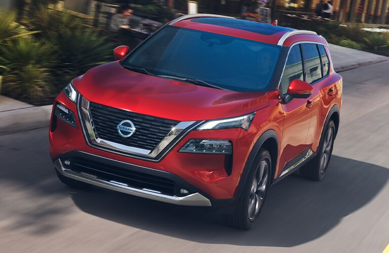 A red-colored 2021 Nissan Rogue driving down a road