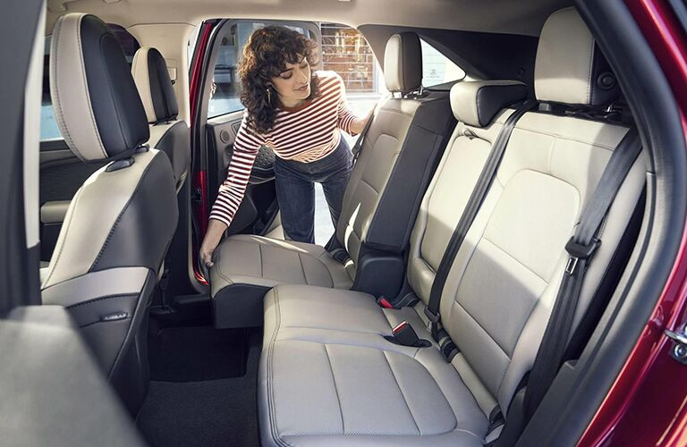 A woman looking into the rear interior of a red 2020 Ford Escape.