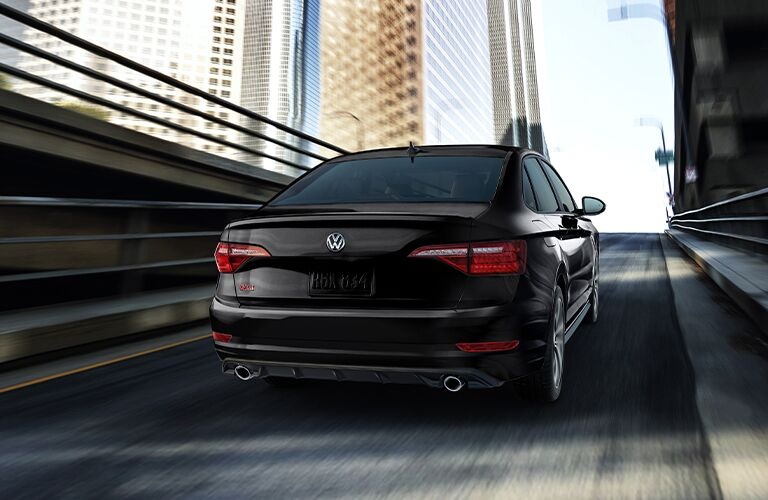 A 2021 Volkswagen Jetta GLI driving on an inclined road toward a city