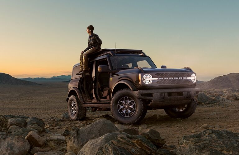 A person sitting on top of a brown 2021 Ford Bronco in rough terrain.