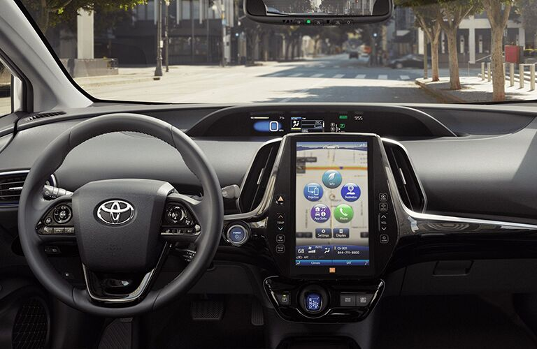 The front interior image of the center console and steering wheel inside a 2020 Toyota Prius.
