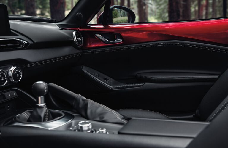 The front interior inside a red 2020 Mazda MX-5 Miata.