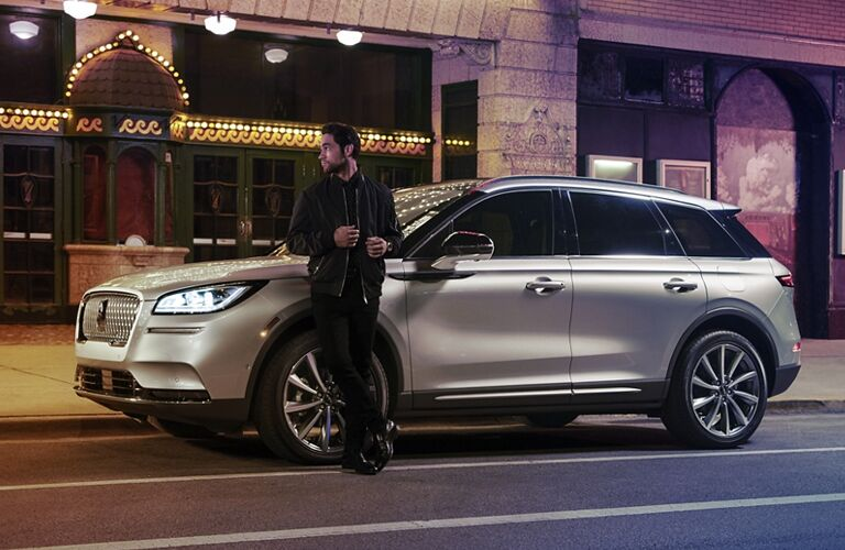 2020 Lincoln Corsair parked on the side of the road with a man standing in front of the tire