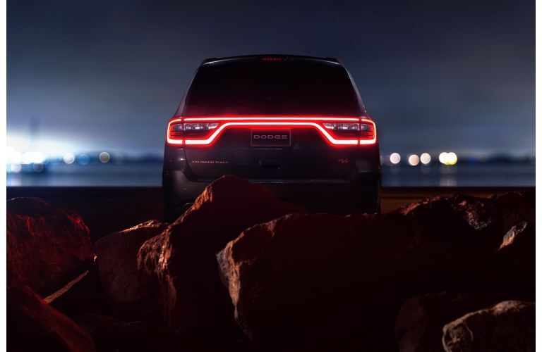 2020 Dodge Durango RT exterior rear shot with LED taillight strip let up in red and framed by a mass of red rocks and stone
