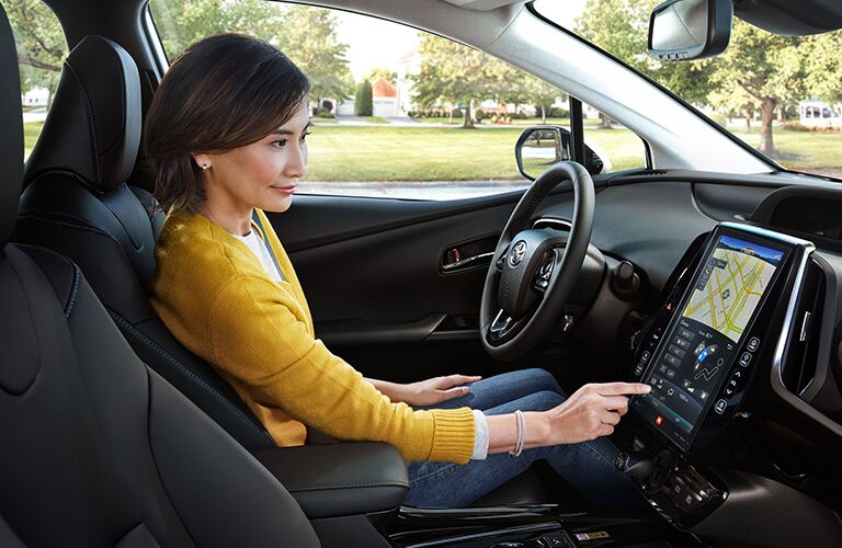 An interior image of a woman driving a 2020 Toyota Prius.