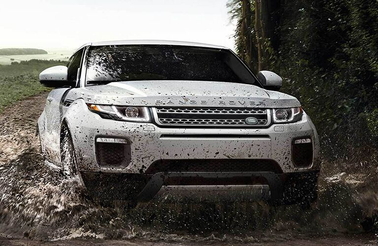 White 2019 Land Rover Range Rover Evoque driving on a muddy road