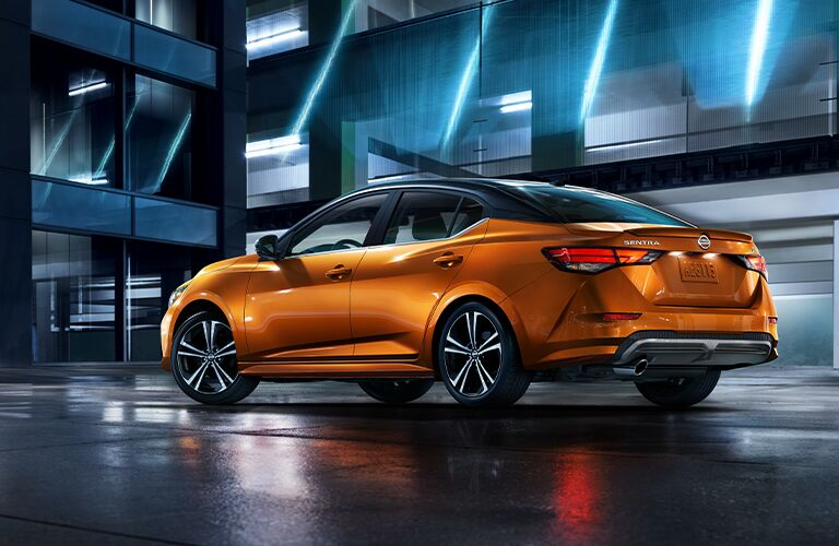 The rear and side exterior view of an orange 2021 Nissan Sentra.