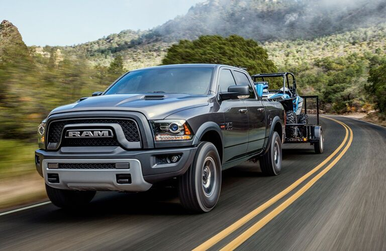 Front view of black 2018 Ram 1500 towing a trailer with a quad bike on it