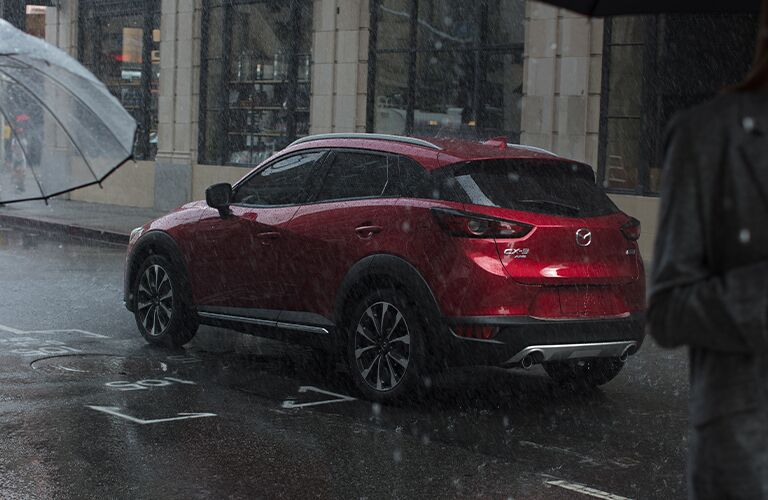 The rear and side view of a red 2020 Mazda CX-3 parked in the rain.