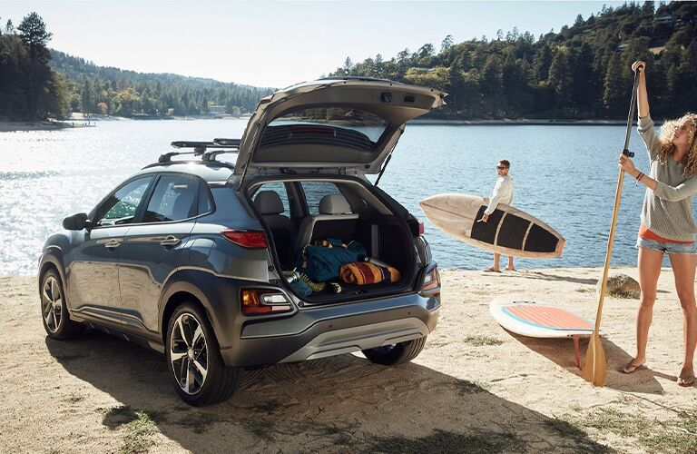 2021 Hyundai Kona with trunk open parked on a beach near water and two people