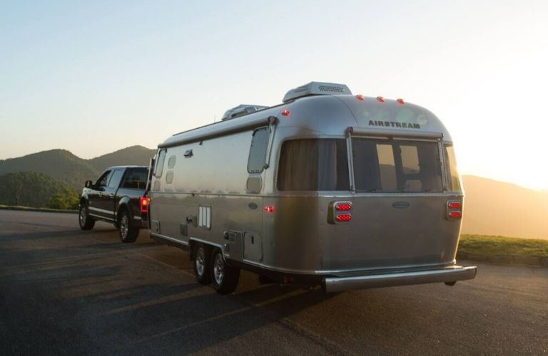 Exterior view of the rear of a 2020 Airstream Flying Cloud towed by a pickup truck