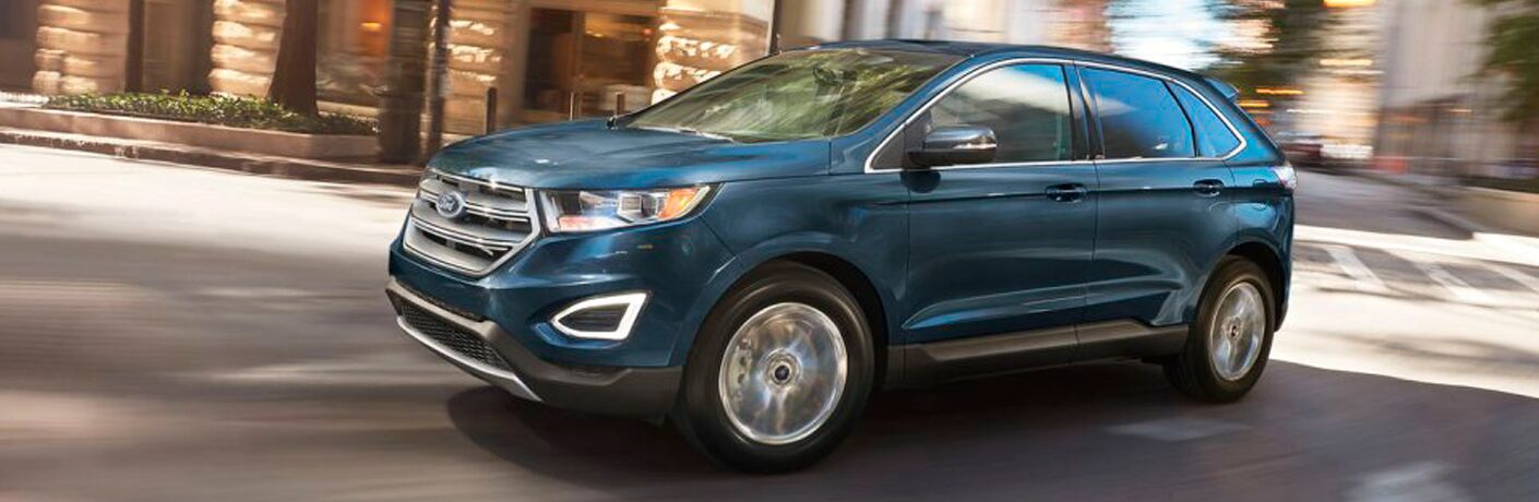 blue Ford Edge driving through downtown streets