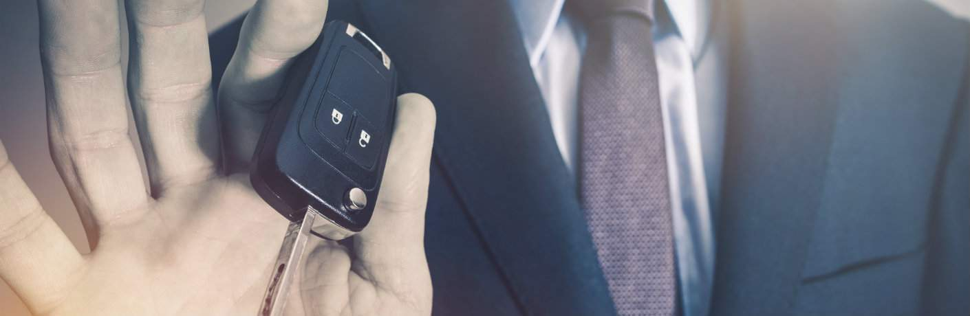 man in suit holding car keys