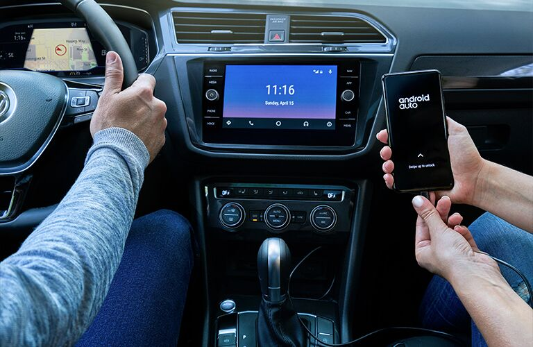 Man driving the 2020 Volkswagen Tiguan while a woman in the passenger seat hooks her phone up to the touchscreen display