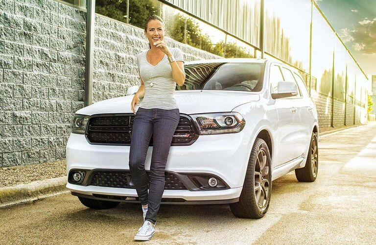 person leaning against a white dodge durango