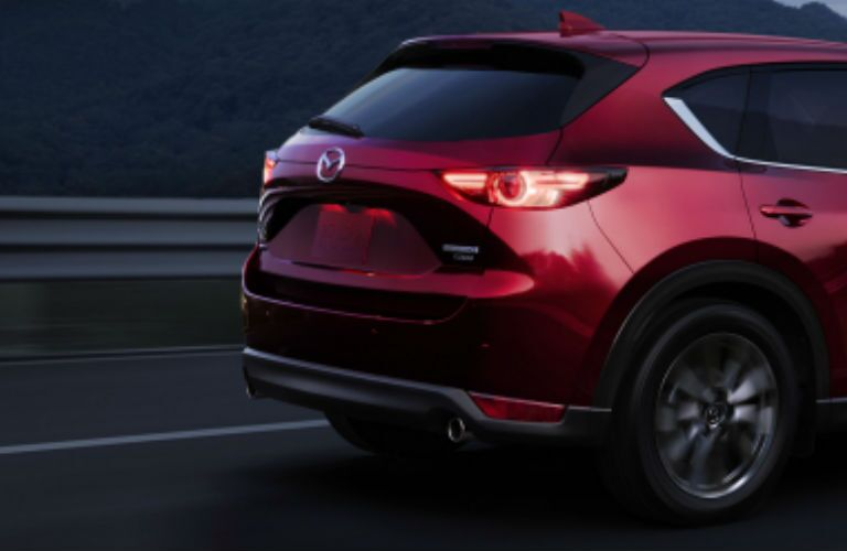 The rear and side view of a red 2021 Mazda CX-5.