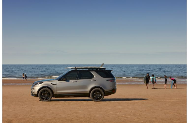 2021 Land Rover Discovery driver side profile on beach with swimmers