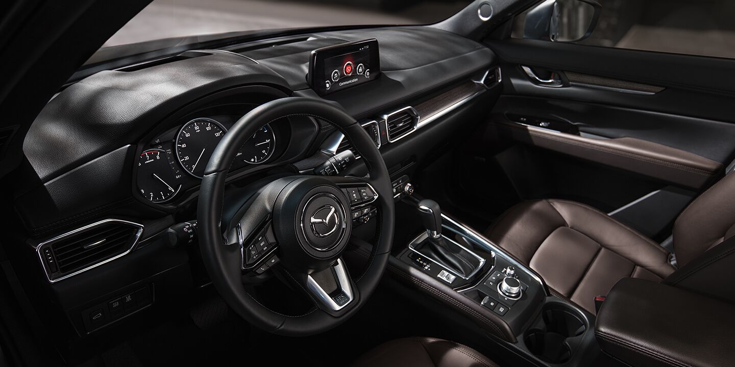 The front view of the steering wheel and center console of a 2020 Mazda CX-5.
