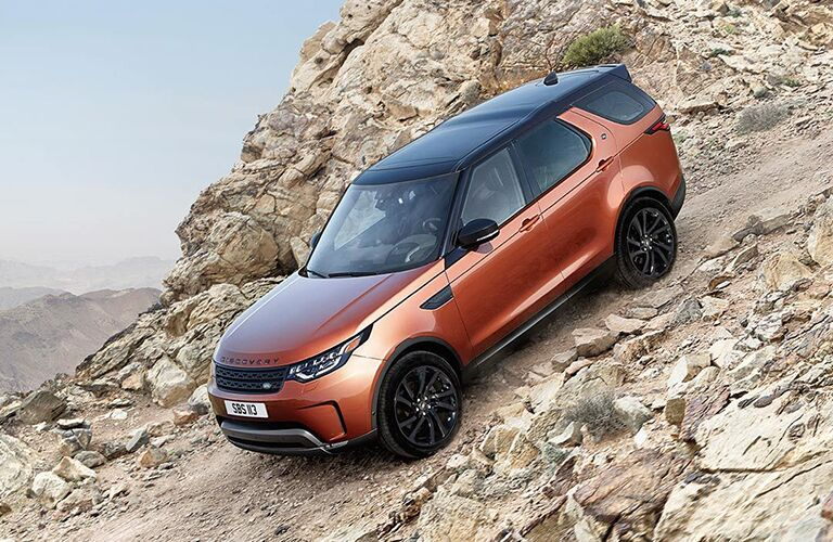 Orange 2019 Land Rover Discovery driving down a rocky hill