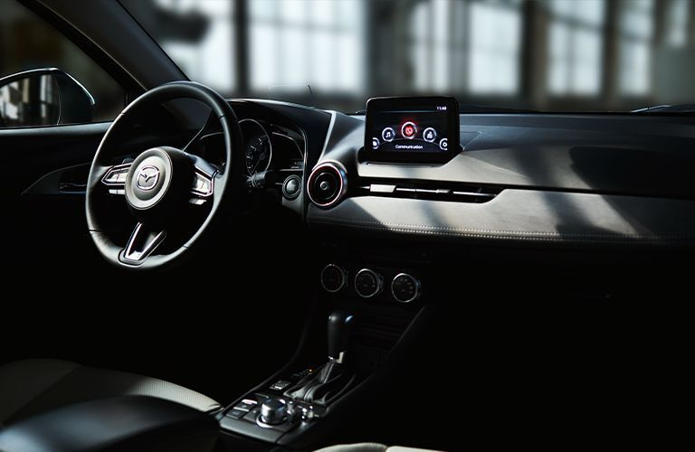 The front interior view of the steering wheel and front seating inside a 2021 Mazda CX-3.