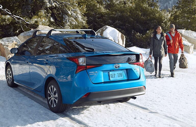 A rear image of a blue 2020 Toyota Prius with a couple walking towards it in the snow.