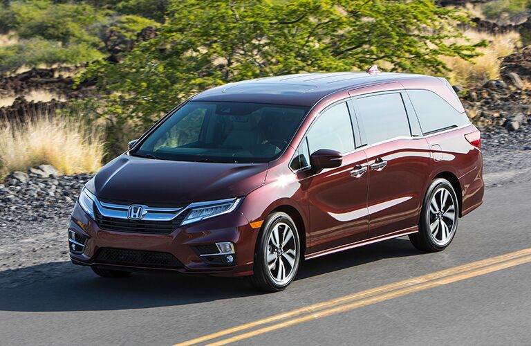 The front and side view of a maroon 2019 Honda Odyssey.