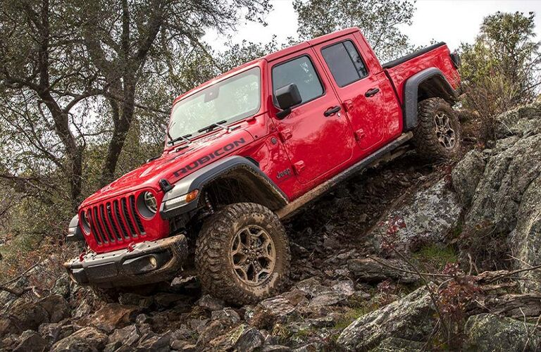 A 2021 Jeep Gladiator driving on a steep rocky incline near some trees