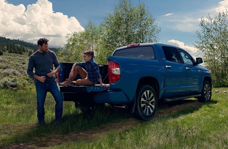 A father standing next to his son, who is sitting on the tailgate of a blue 2021 Toyota Tundra.