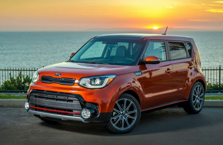 Red 2019 Kia Soul parked on concrete with body of water in background
