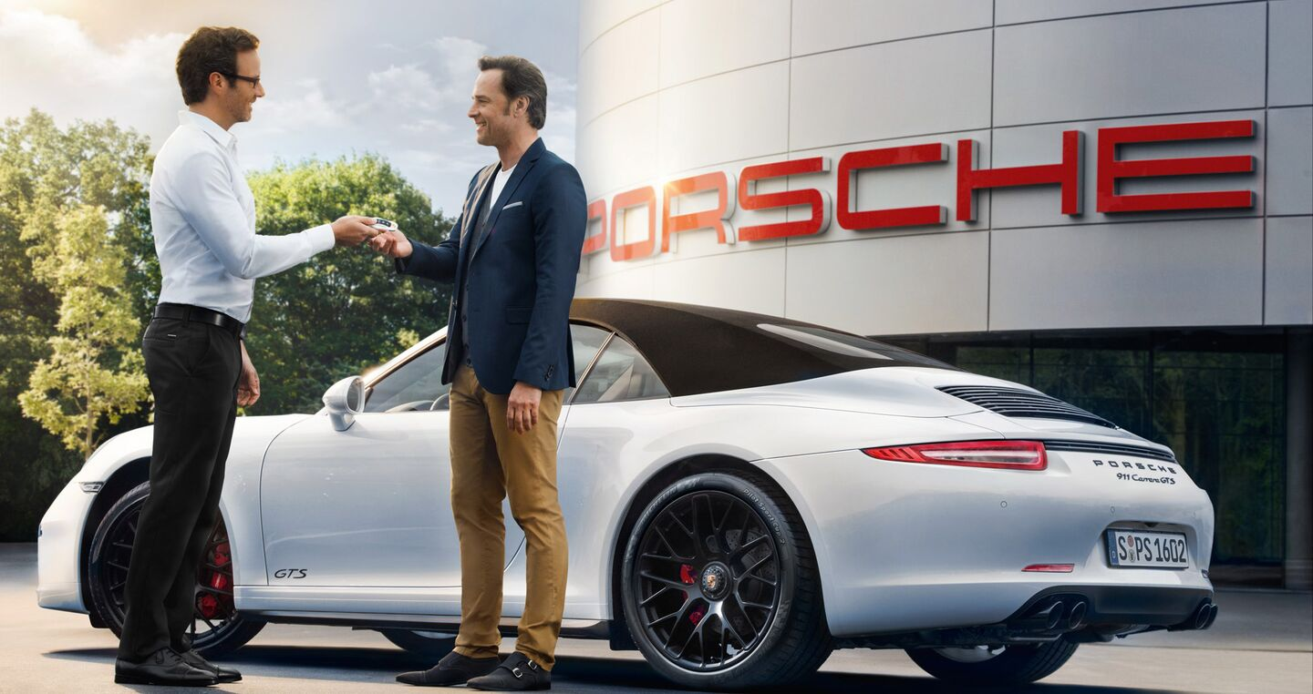 A salesperson handing keys over to the customer in front of a Porsche vehicle