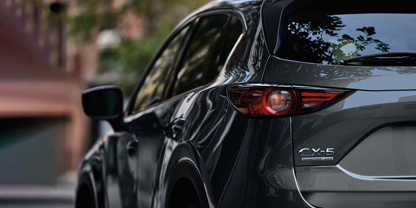 The rear view of a gray 2020 Mazda CX-5 parked in an urban area.