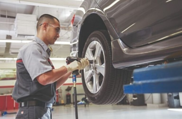 Image of a Toyota service technician removing a tire