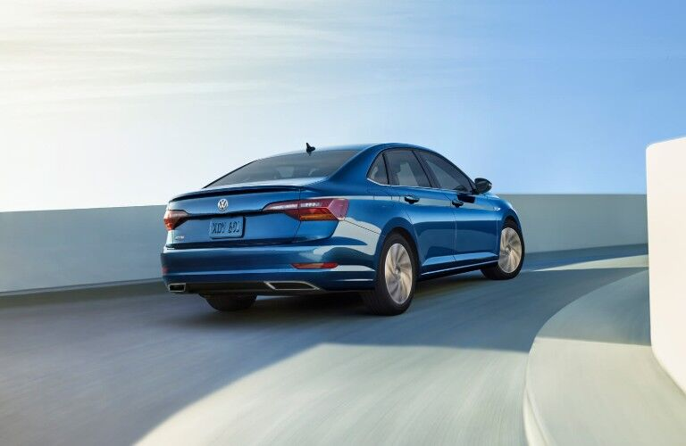 Rear passenger angle of a blue 2019 Volkswagen Jetta driving on a curving bridge