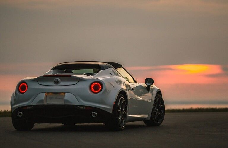 Rear passenger angle of a white 2019 Alfa Romeo 4C Spider with a sunset in the background