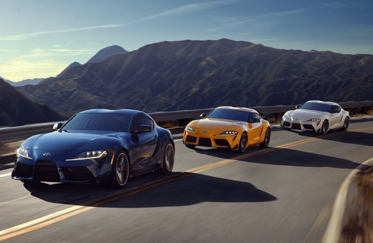 Exterior view of the front of three 2020 Toyota Supra models driving down the highway