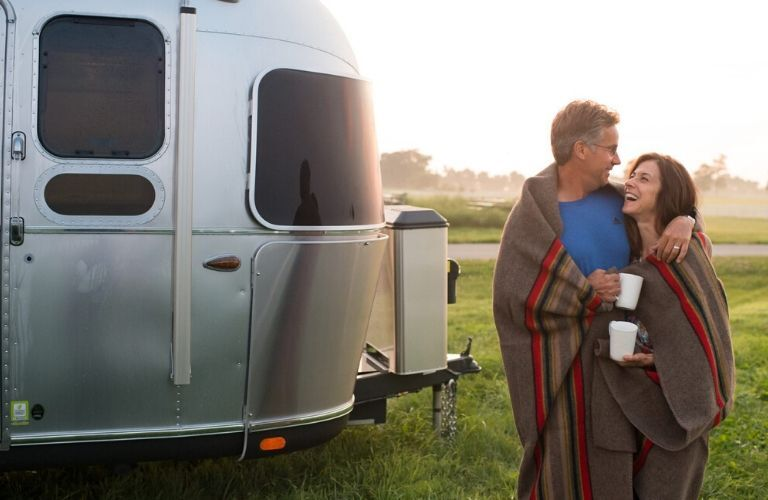 Image of a happy couple standing outside the front of a silver 2020 Airstream Classic