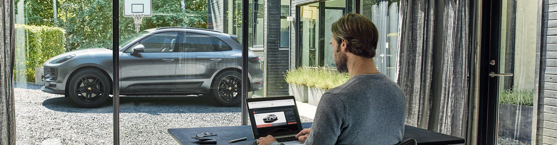 Man using laptop and a Porsche vehicle outside of the building