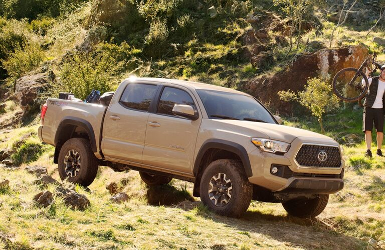 Tan 2019 Toyota Tacoma driving down hill with passenger looking on