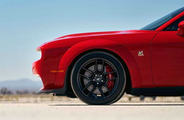 A side view of the front wheel style of a red 2020 Dodge Challenger.